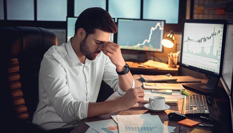 Comerciante sério com os olhos fechado massageando a ponte nasal causado por perda de dinheiro ou cansado por excesso de trabalho