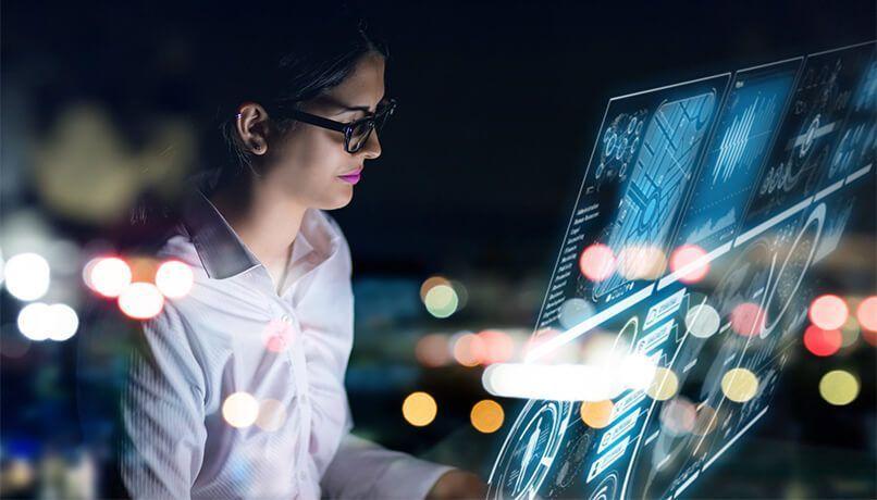 Mulher com traje social visualizando uma interface de usuário holográfico futurista