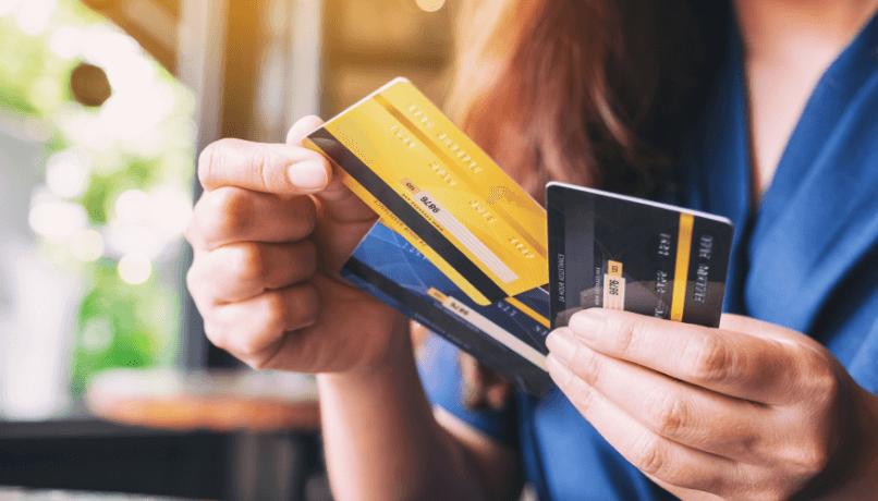 Imagem aproximada de uma mulher segurando e escolhendo o cartão de crédito para usar