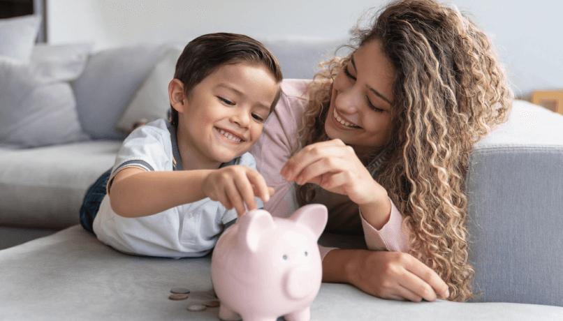 Retrato de uma feliz mãe e filho, economizando dinheiro em um cofrinho e sorrindo - conceitos de finanças domésticas